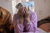 Elderly woman with her face in her hands
