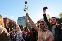 A woman holding a rose in the air at a demonstration