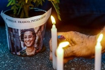 A hand holding a candle near a picture of Marielle Franco