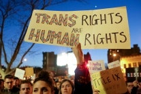 """A demonstrator holding a sign that says; """"Trans Rights Are Human Rights"""""""