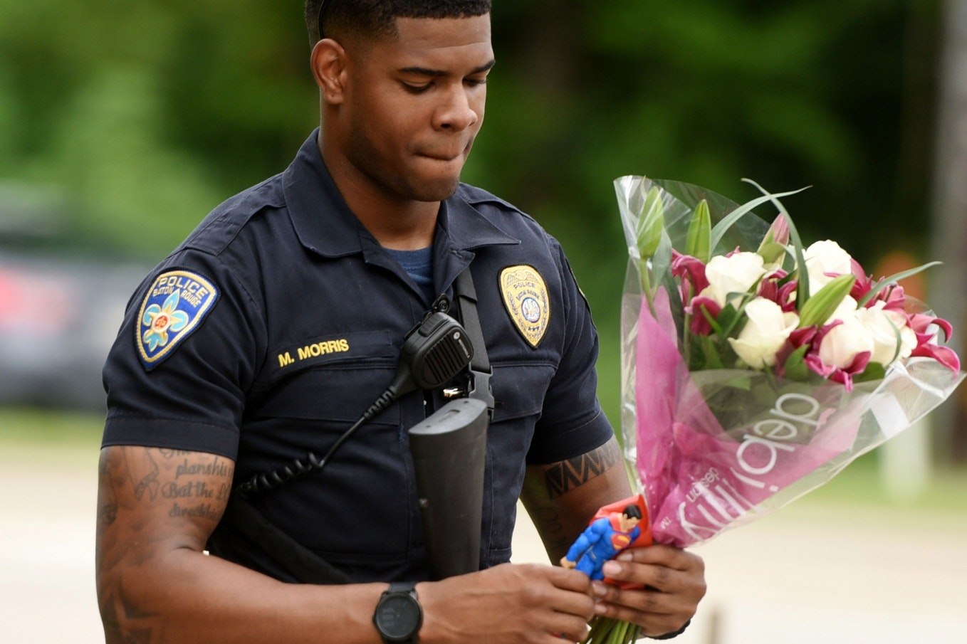 A police officer holding flowers and a Superman action figure