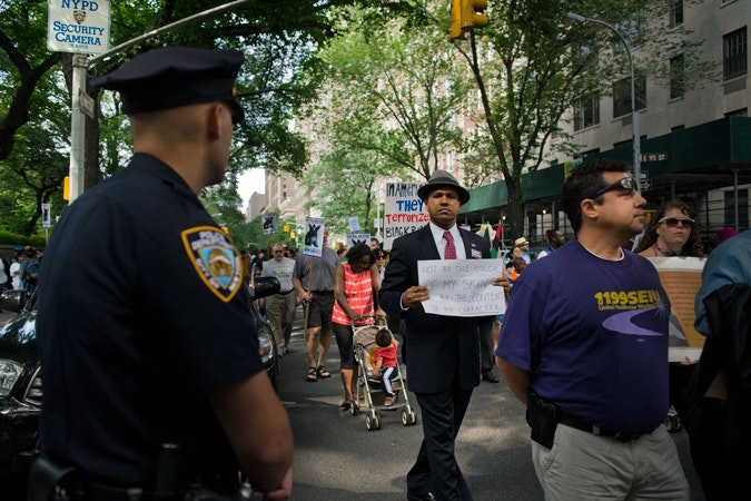 Man walking with sign by police officer