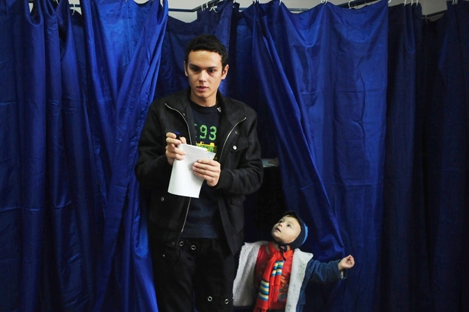 A man with child coming out of booth