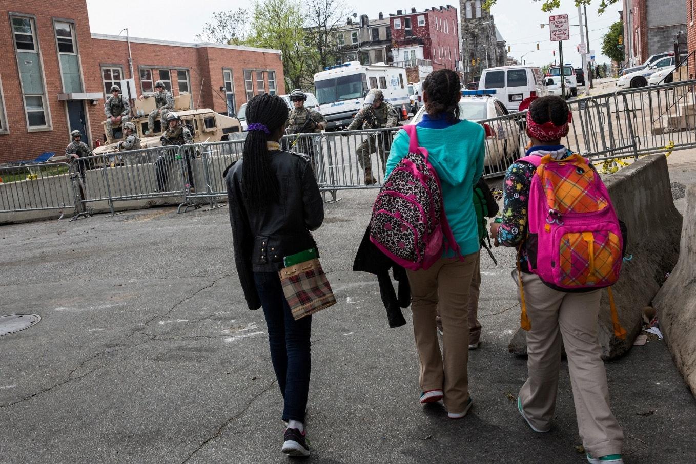 Children walk past National Guardsmen in Baltimore