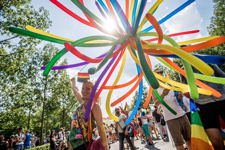 Fiatal nő színes léggömböt tart a tömegben