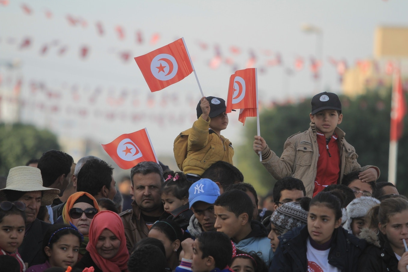 Boys waving flags in a crowd