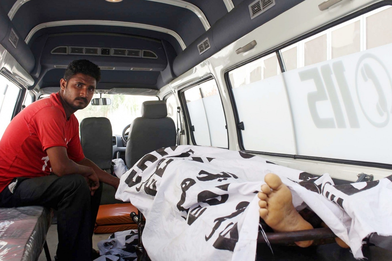 A man next to a covered body in an ambulance