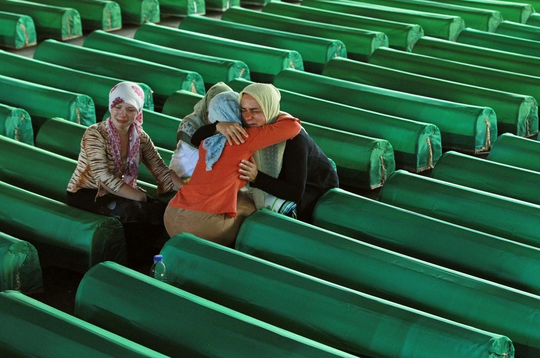 Women kneel between rows of covered coffins