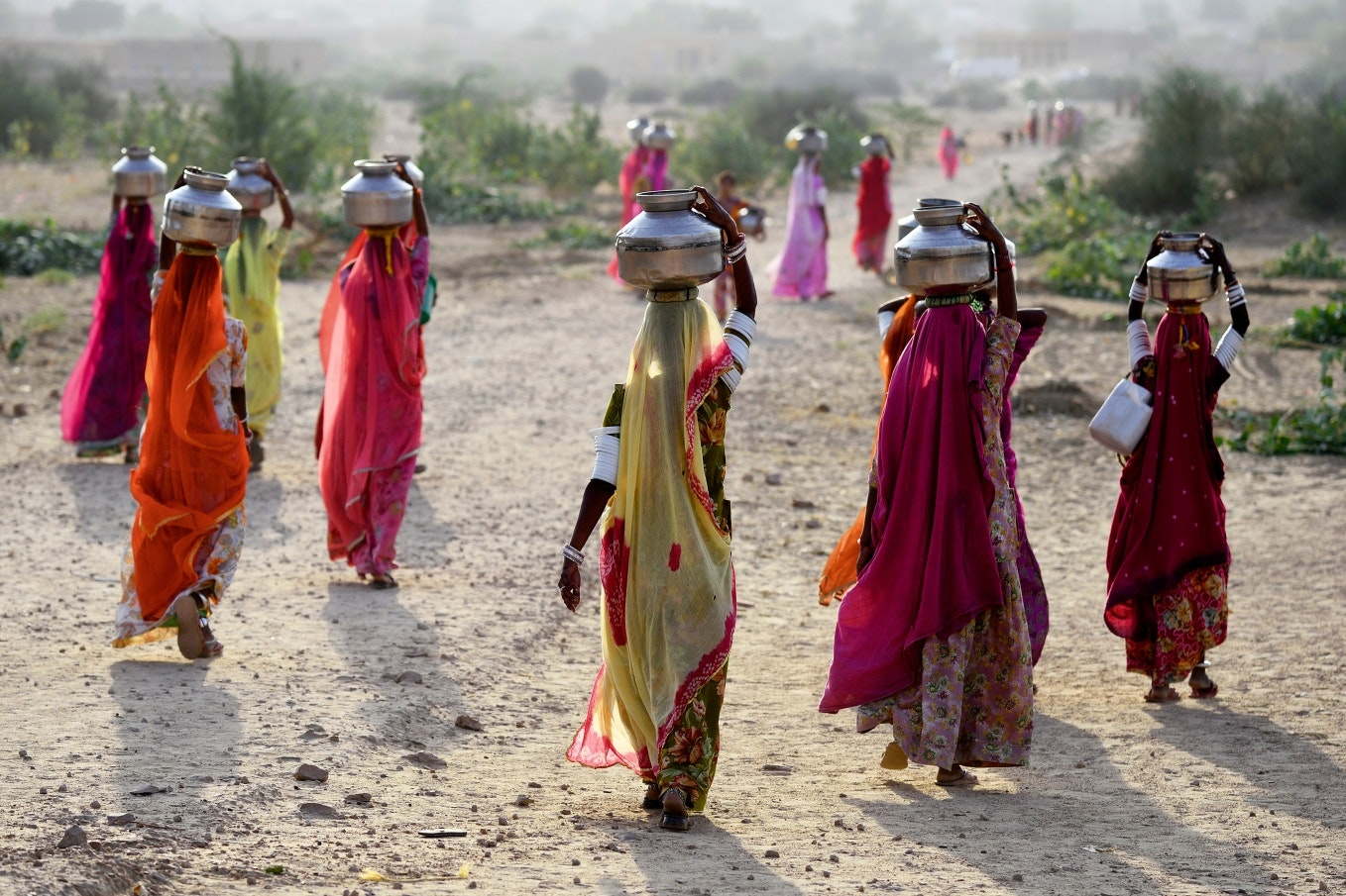 Women in bright saris carrying water jugs on their heads