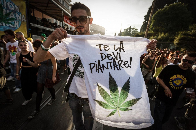 A man holding up a t-shirt printed with a marijuana leaf