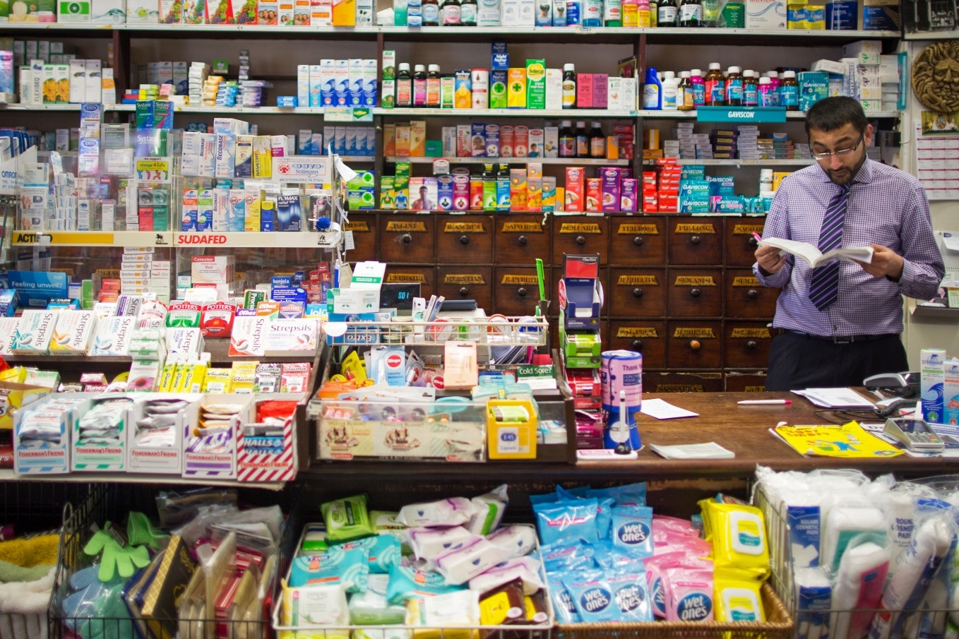 A man behind the counter at a pharmacy