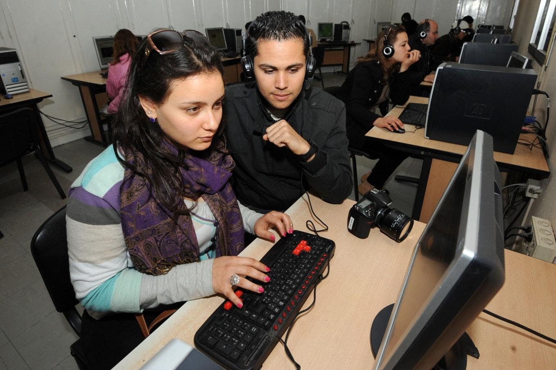 شخصان يستخدمان الكمبيوتر