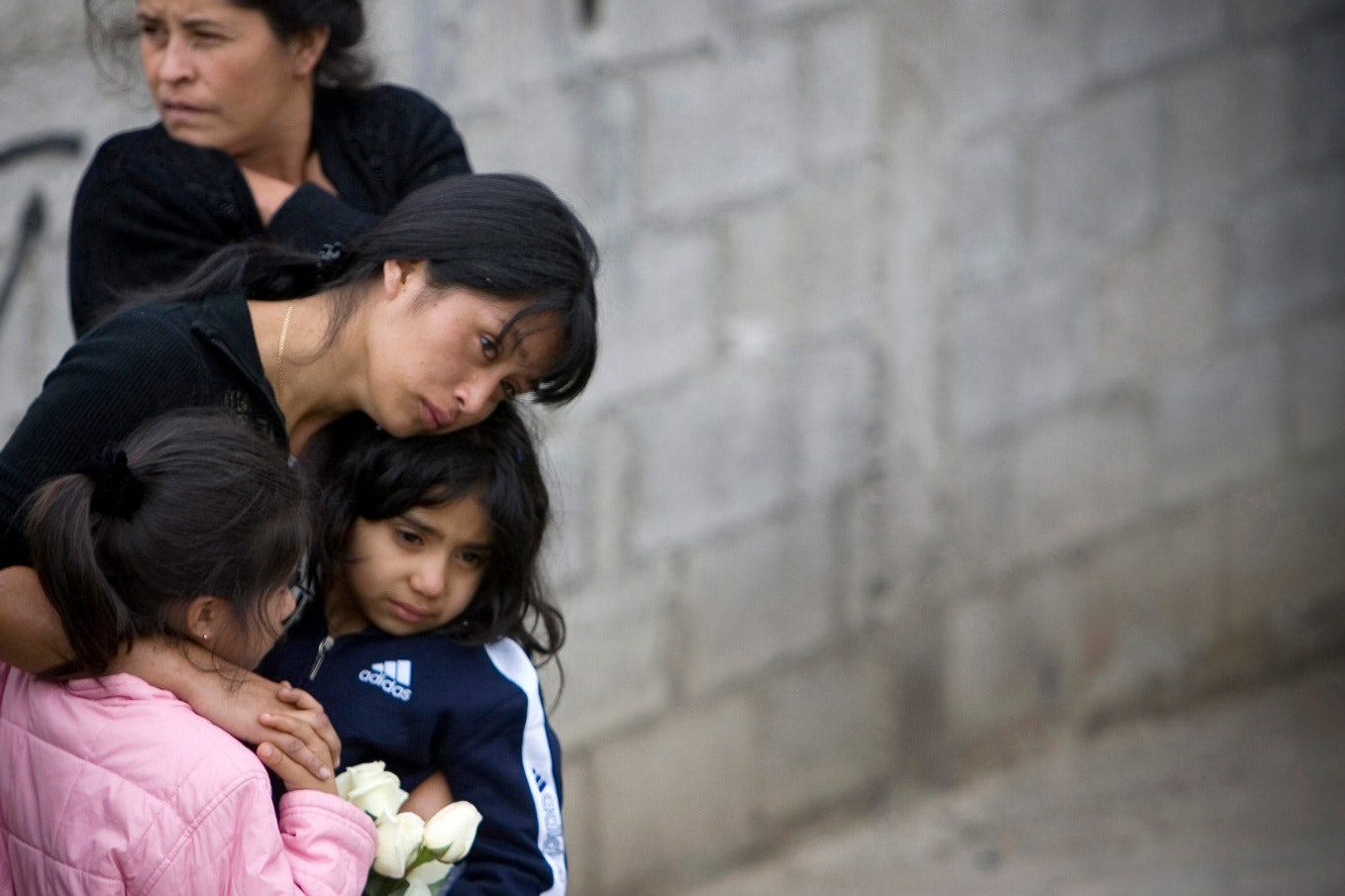 A woman hugging two young girls