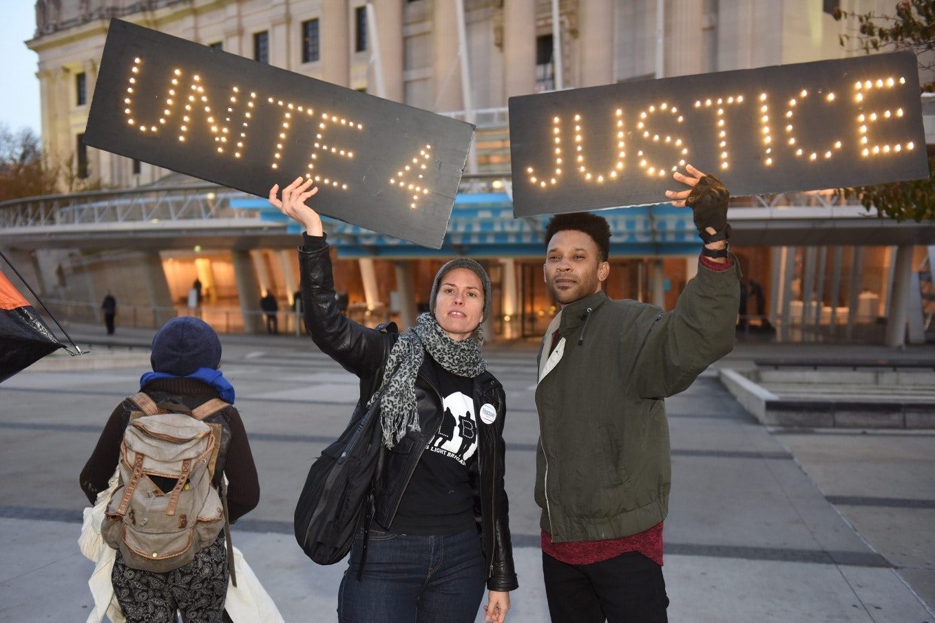 Two people holding signs