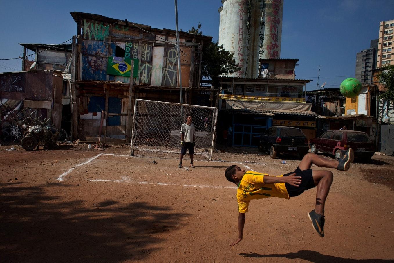 Dois jovens jogam futebol num lote vazio