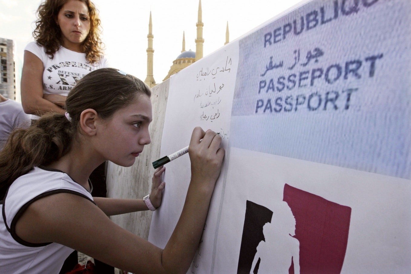 A young woman writing on a large sign in front of a mosque