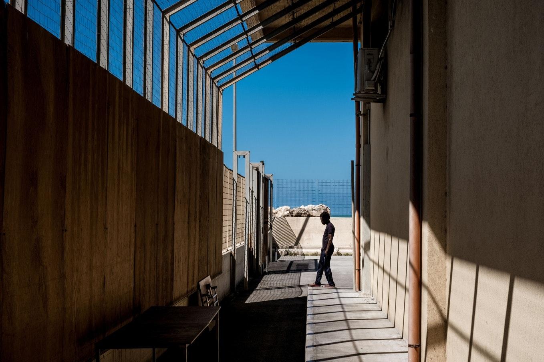 Egy ember áll a falakkal és kerítésekkel elzárt területen