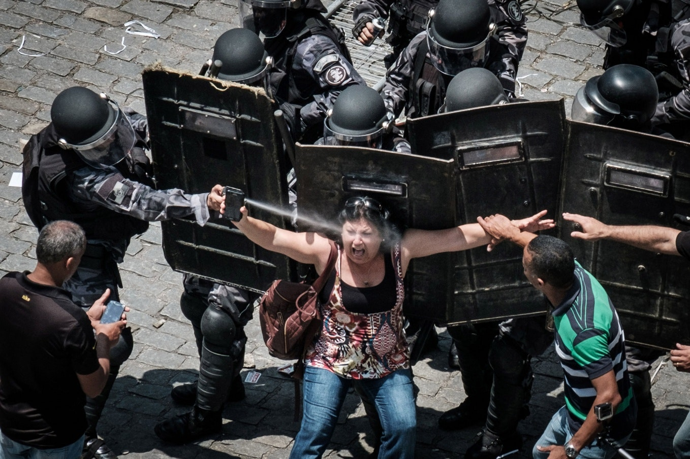 A riot police officer spraying a woman in the face with pepper spray