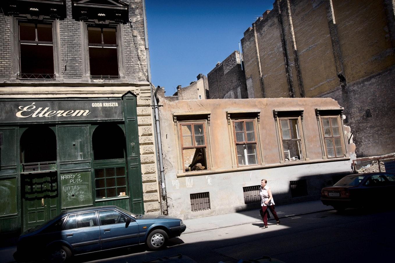 Egy asszony elsétál egy omladozó épület előtt