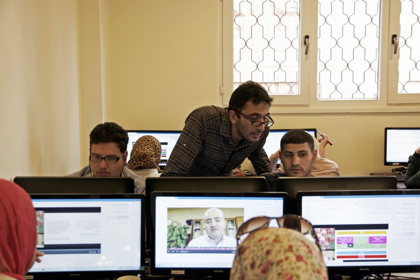 A teacher with students at computer stations