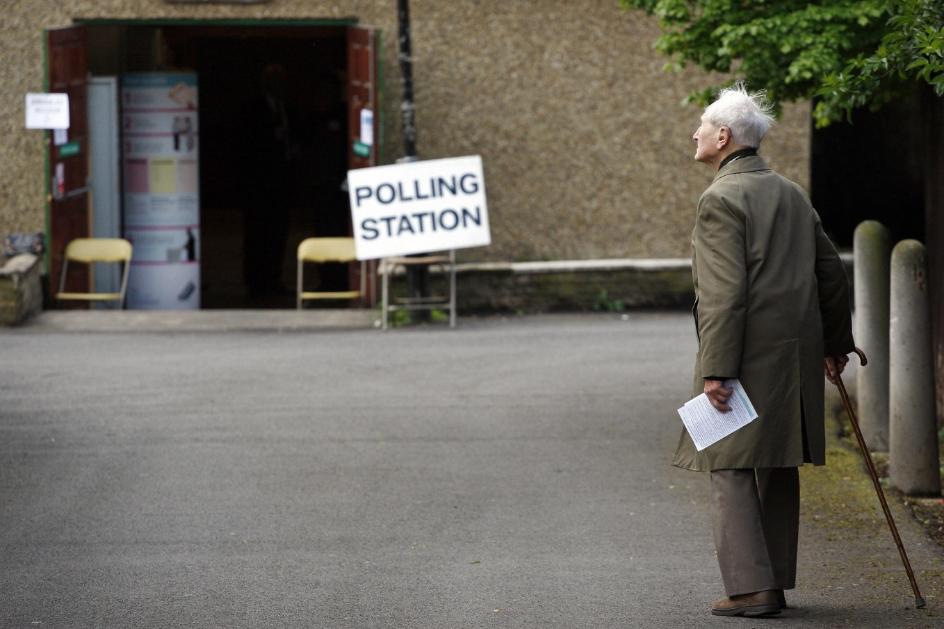 An elderly man walking with a cane towards a polling station