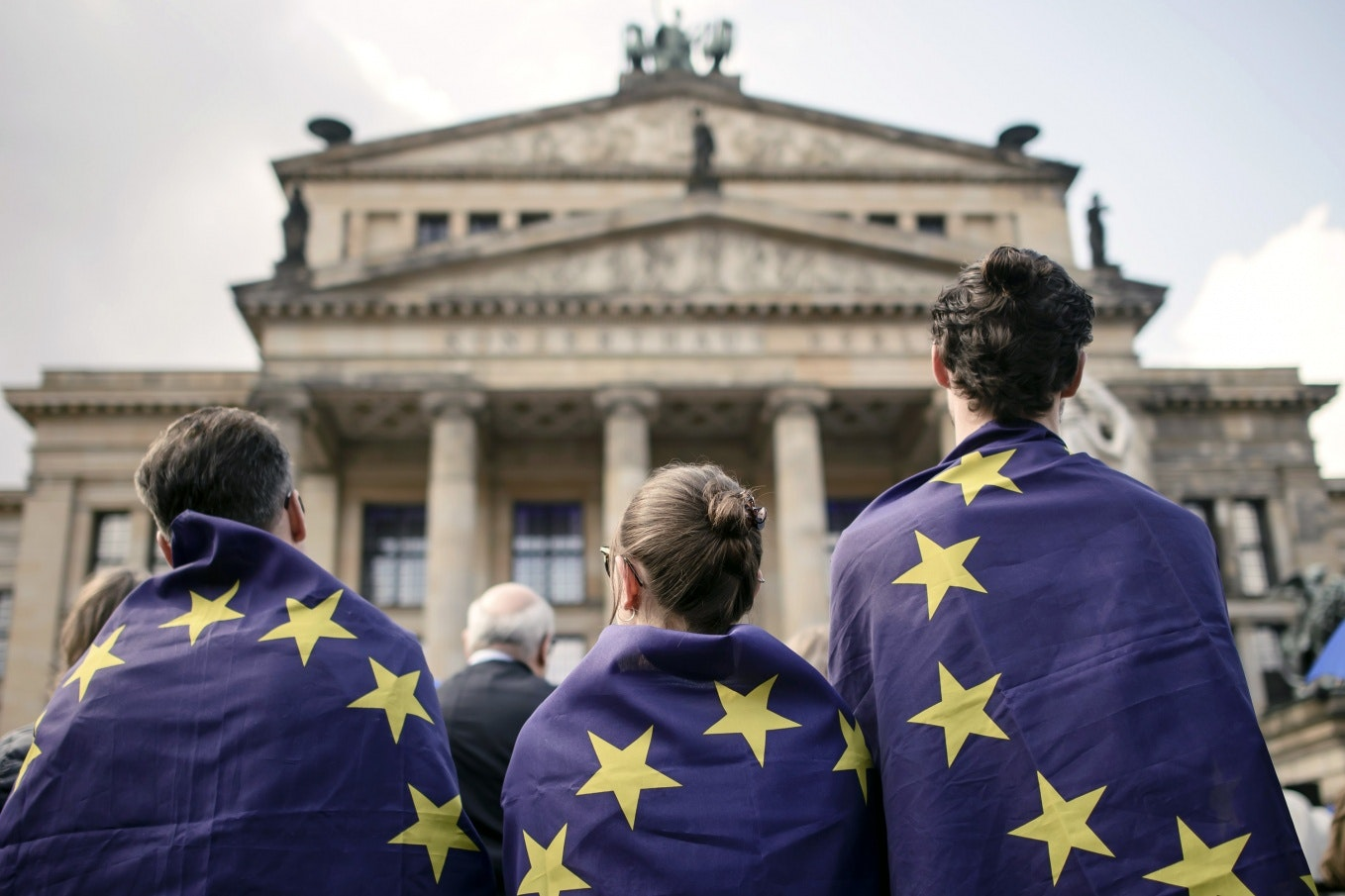 Three people wrapped in EU flags.