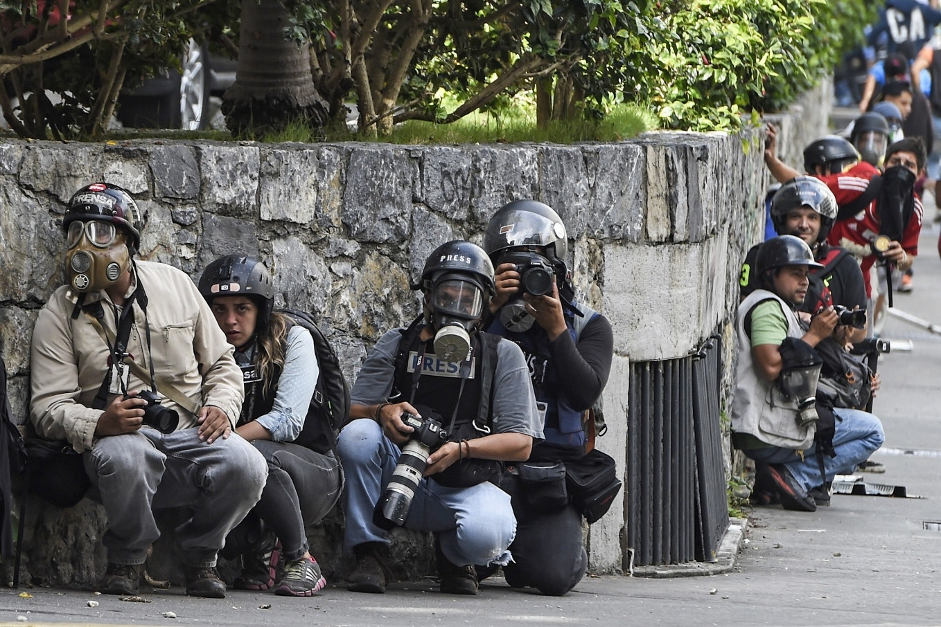 People in gas masks and helmets crouch at a stone wall