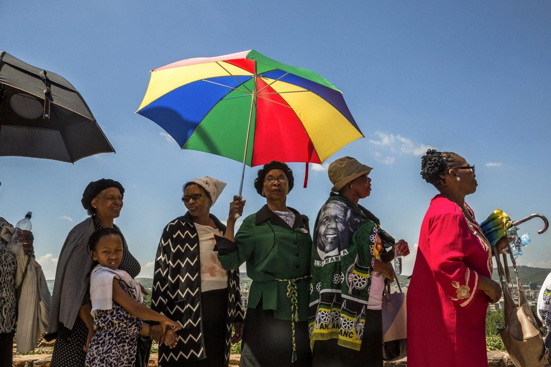 Woman in a line holding a multi-colored umbrella