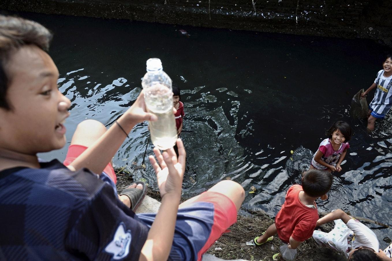 A boy holding a plastic bottle