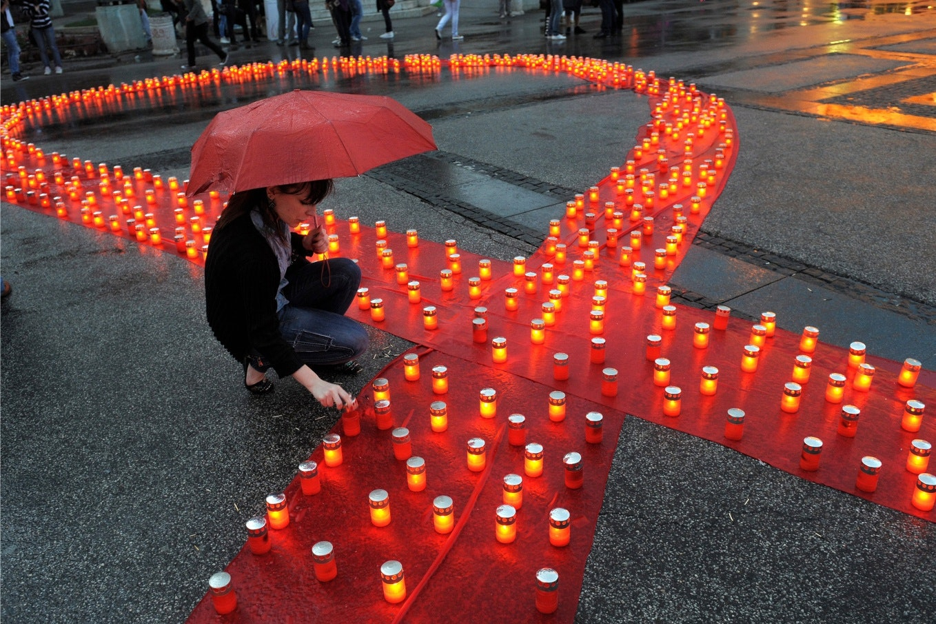 A red ribbon lined with candles on pavement