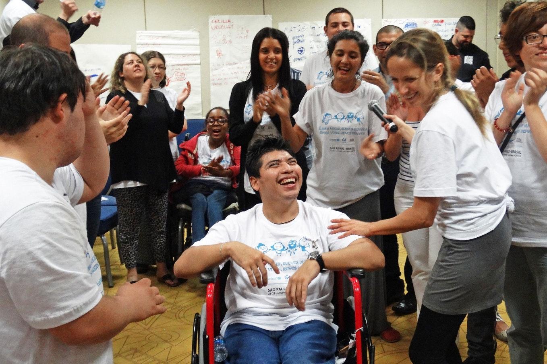 personas rodean a un joven en silla de ruedas