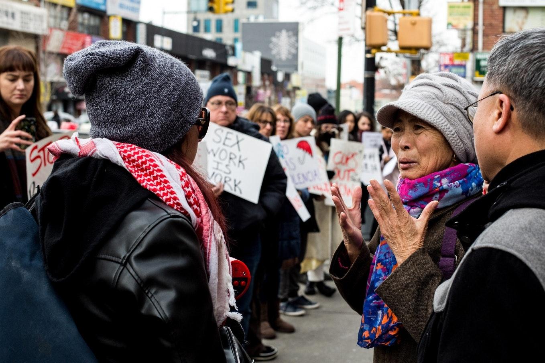 People gather on a city sidewalk