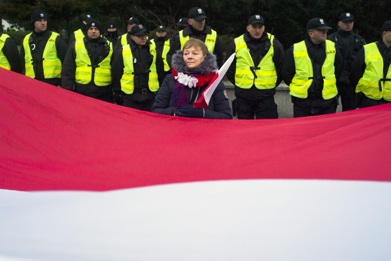 A large Polish flag in front of a row of police