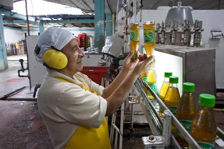 Un trabajador inspecciona las botellas de Coca Sek