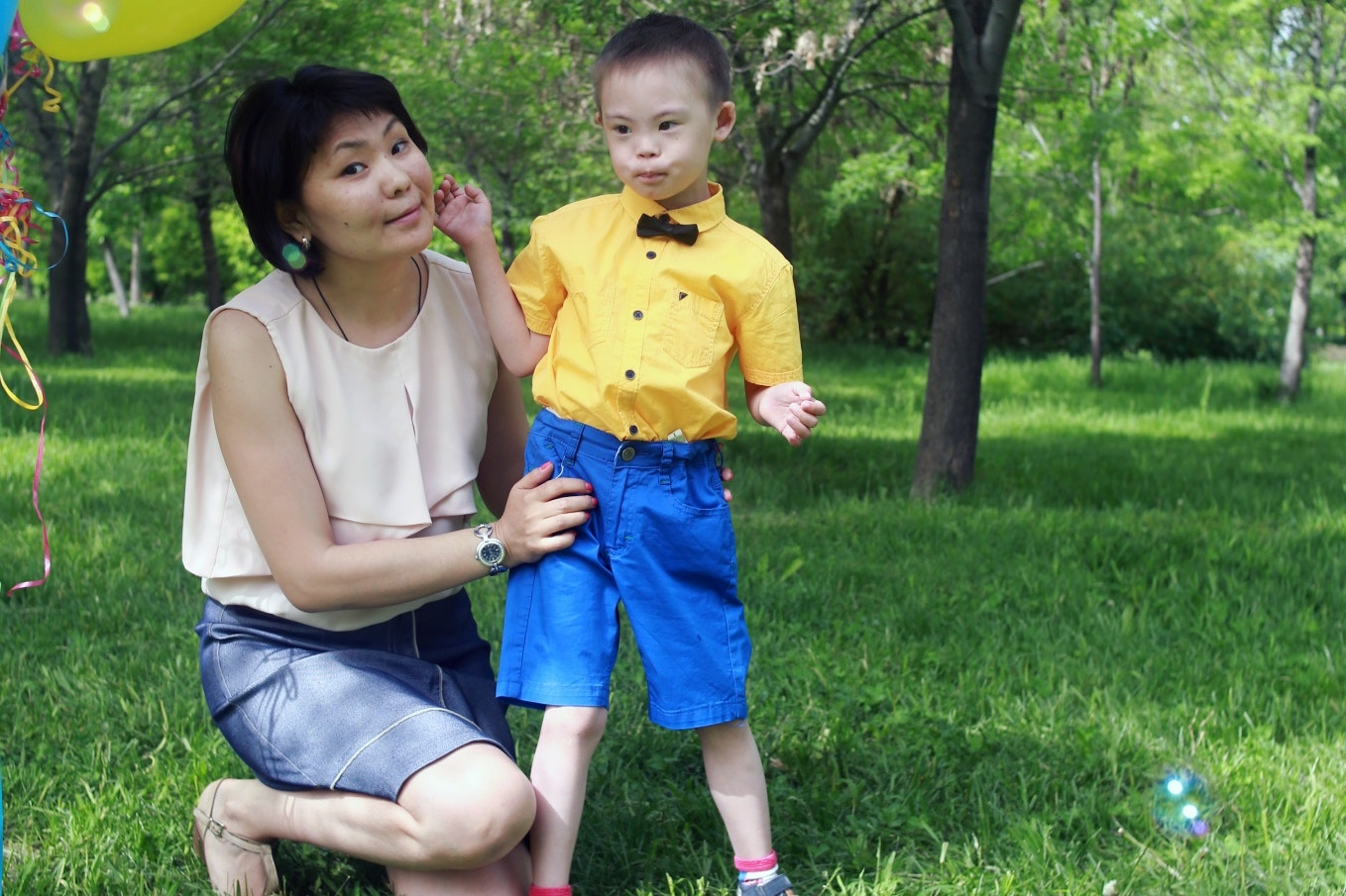 Aigul Shakibayeva kneeling next to her son.