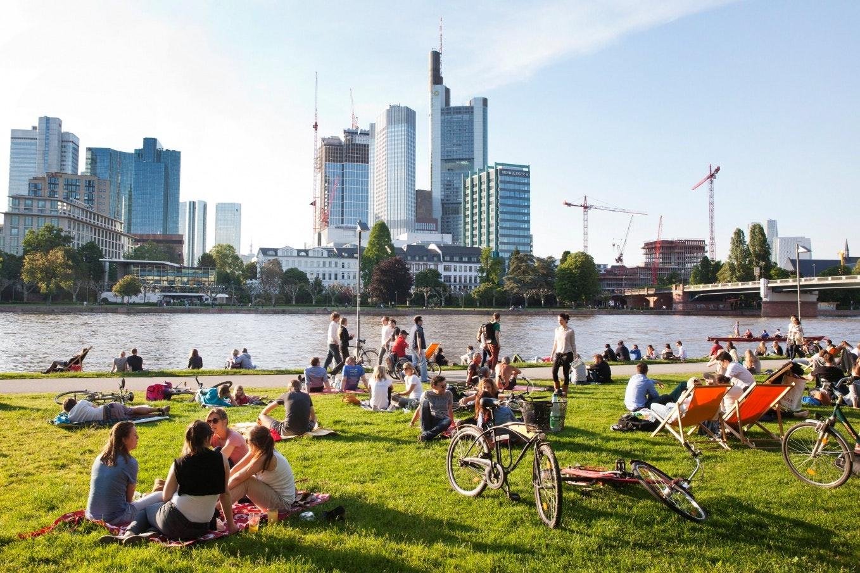 Menschen sitzen auf grünem Gras an einem Flussufer