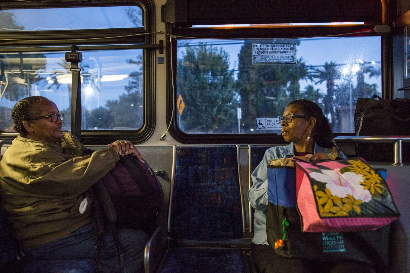 Two women sitting on a bus at dawn