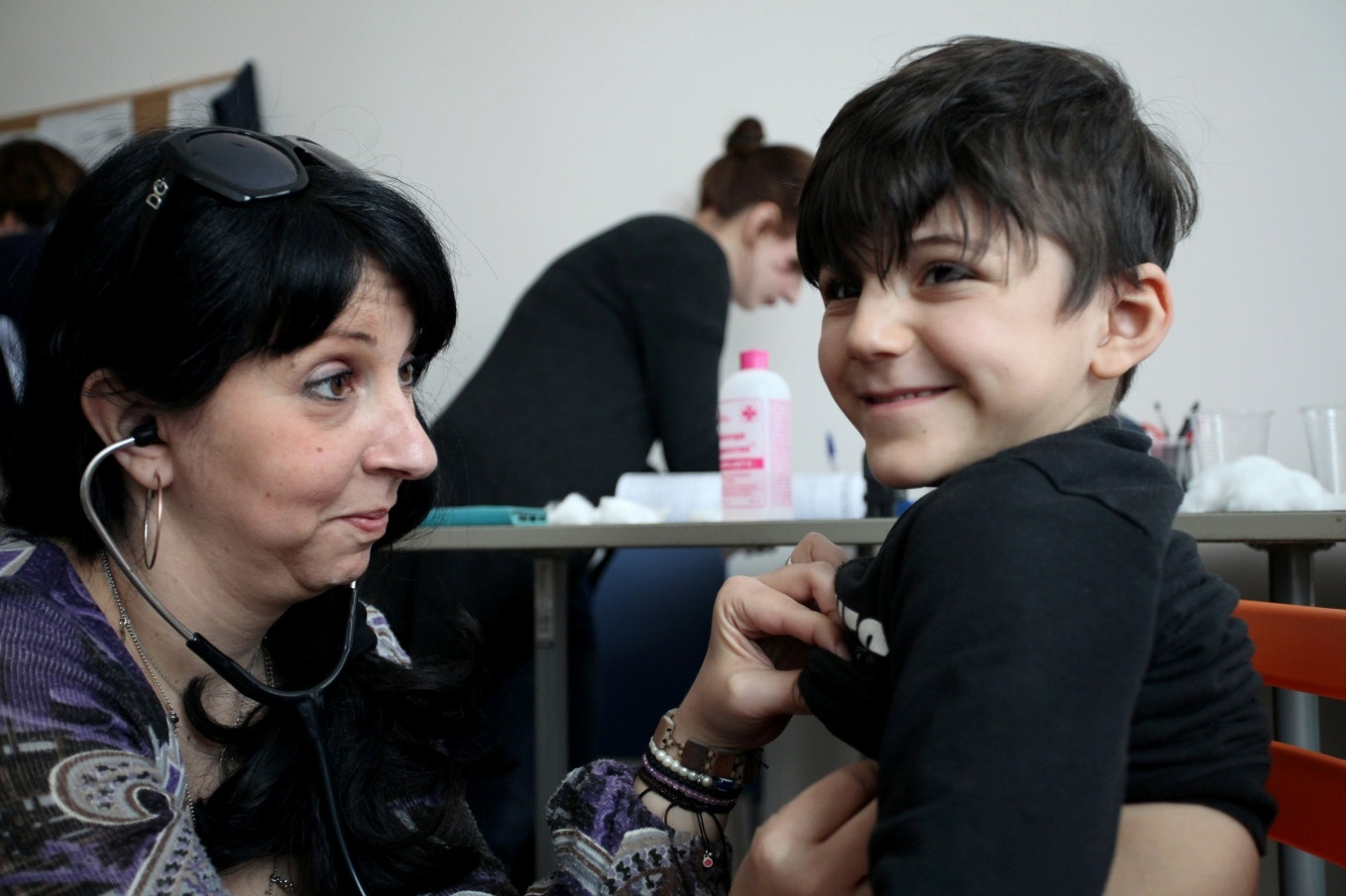 A boy smiles while being examined by a doctor