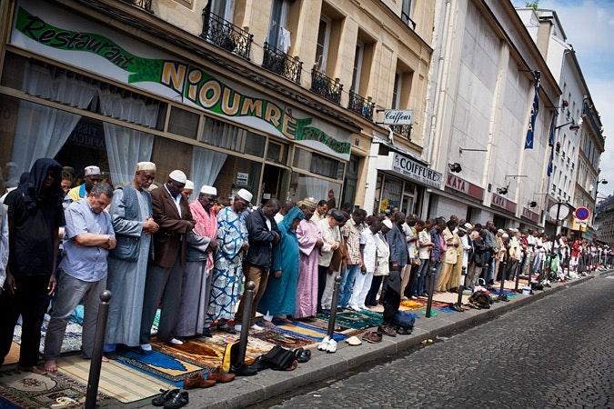 Men standing on sidewalk, praying