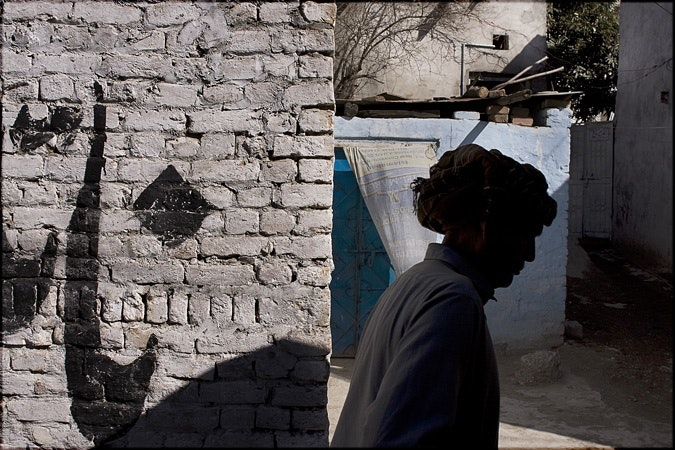 Woman walking by brick wall