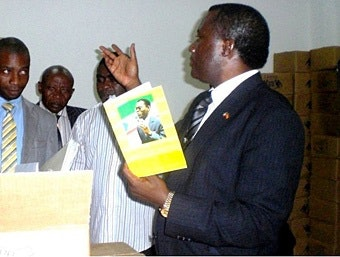 Man holding school notebook with a picture of President Teodoro Obiang on cover