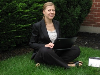 Maria Creciun sitting on the grass with a laptop