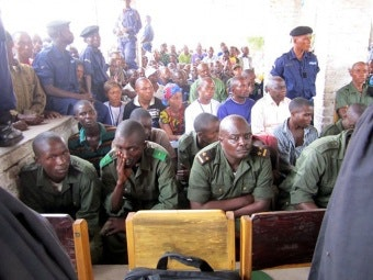 Lt. Col. Kibibi Mutware sitting at the front of a large group at trial