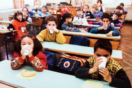 Children at school desks drinking milk