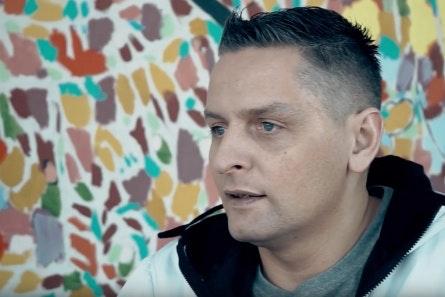 Maciej Dobrowolski by multi-colored wall