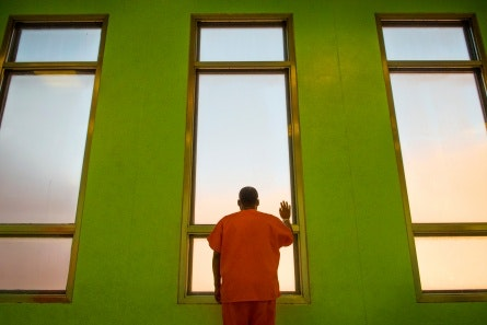 A man in orange standing at a window