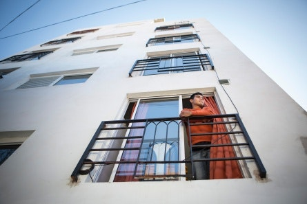 A man stands at an apartment window