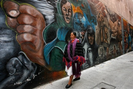 A woman walking in front of a colorful mural