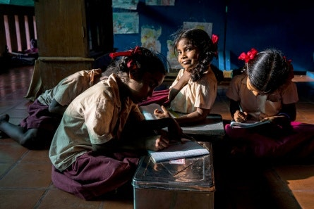 School girls sitting on the floor of a classroom