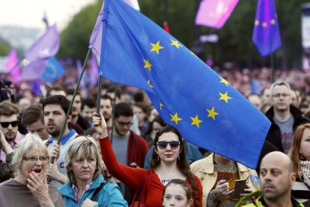A woman holds aloft a European Union flag in a large crowd